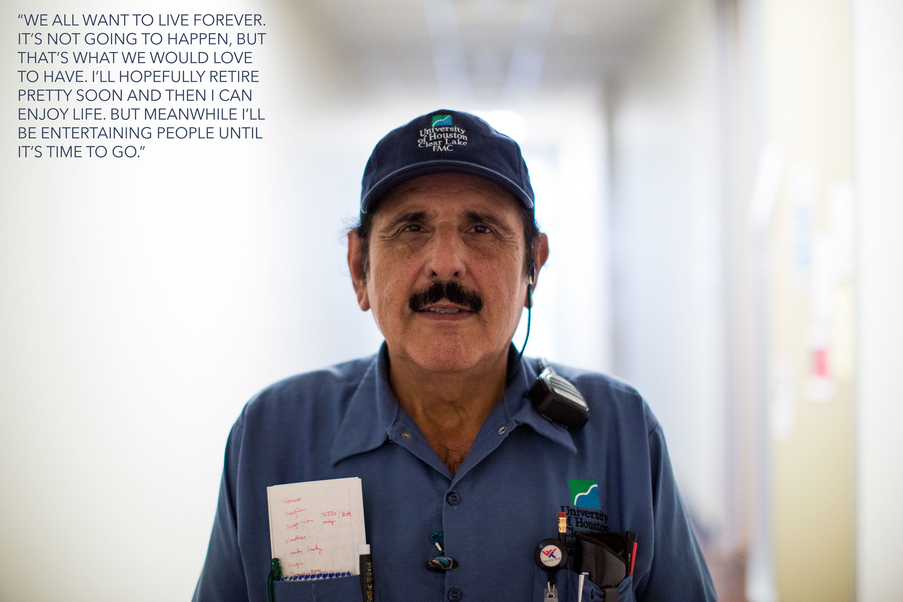 "Photo: UHCL staff member Gabriel Galvan stands in a hallway of the Bayou Building. Galvan says: ""We all want to live forever. It's not going to happen, but that's what we would love to have. I'll hopefully retire pretty soon and then I can enjoy life. But meanwhile, I'll be entertaining people until it's time to go."" Photo & interview by The Signal reporters Maegan Hufstetler and Travis Pennington."