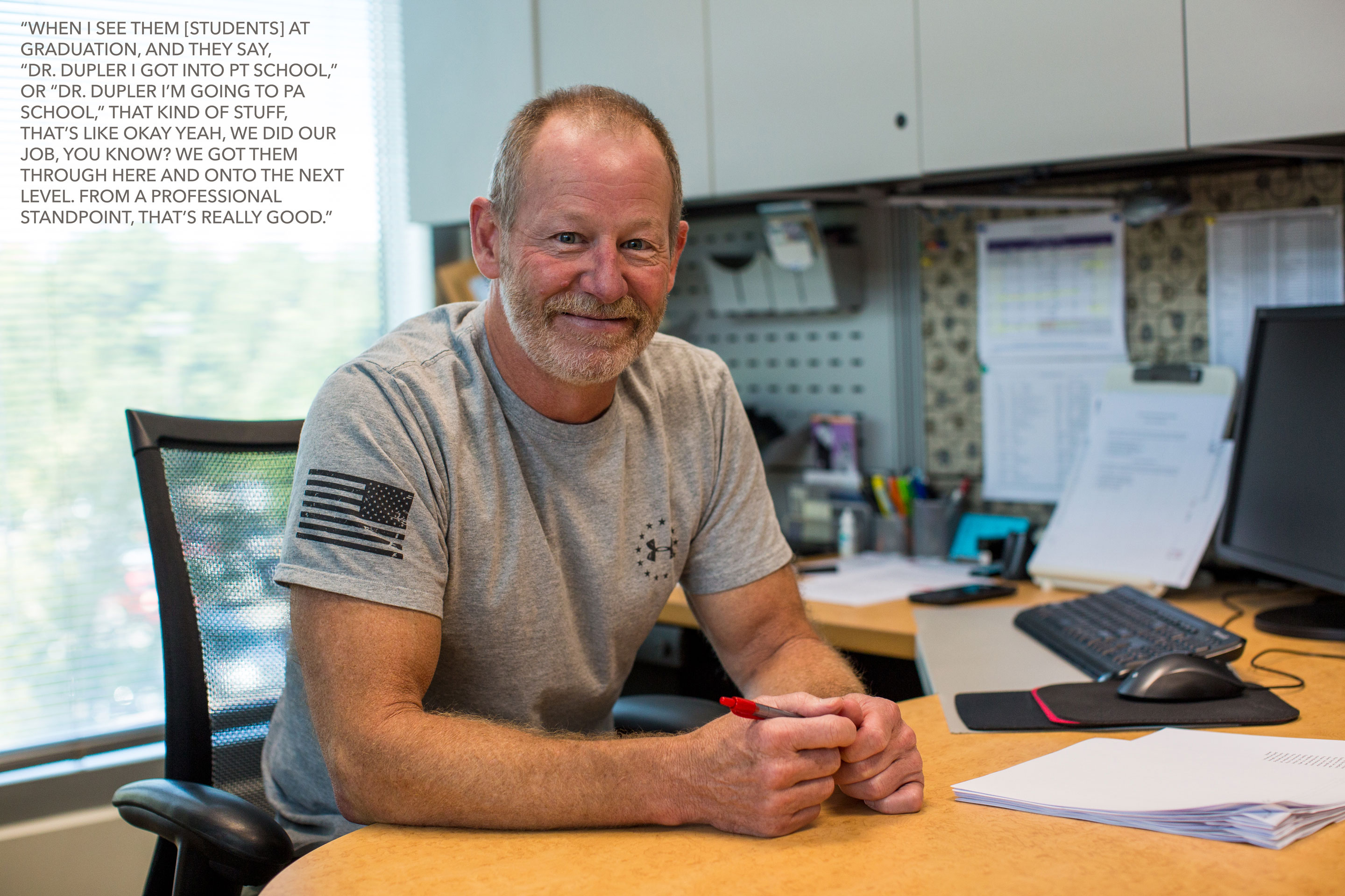 "Photo: UHCL faculty member Terry Dupler sits at his desk. Dupler states: ""When I see [students] at graduation, and they say 'Dr. Dupler, I got into PT school,' or 'Dr. Dupler, I'm going to PA school,' that kind of stuff, that's like, okay, yeah, we did our job, you know? We got them through here and onto the next level. From a professional standpoint, that's really good."" Photo & interview by The Signal reporters Maegan Hufstetler and Travis Pennington."